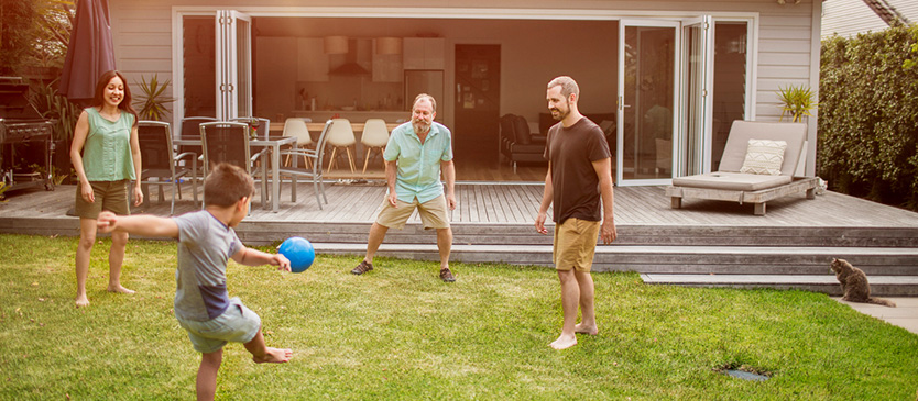 Family in backyard kicking soccer ball around