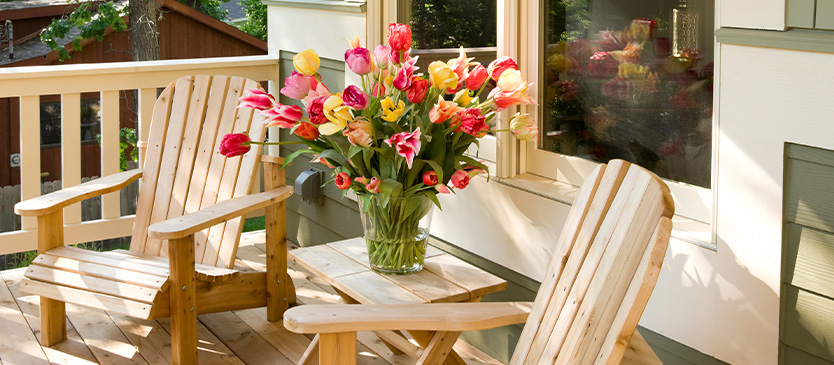 2 chairs on porch next to small table with flowers on it