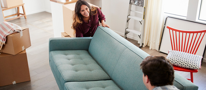 young couple moving blue couch into their new home