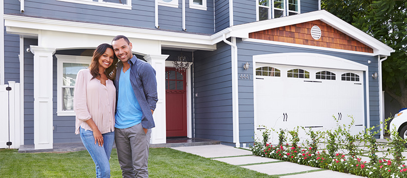 Couple standing in front of home embracing and smiling