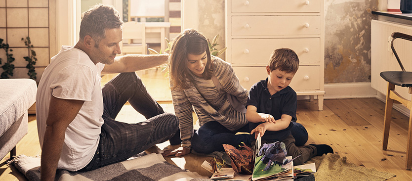 young family reading a pop-up book on their sons bedroom floor