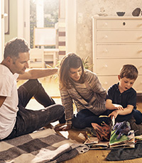 Family reading popup book with son